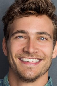 hombre feliz sonriendo tras limpieza bucal
